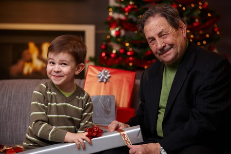 Happy grandfather and grandson wrapping gifts together at christmas, smiling.   photo
