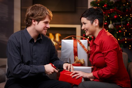 Happy young couple wrapping christmas gifts, looking at each other, smiling.   photo