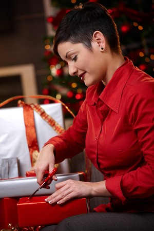 Young woman sitting on couch at home, wrapping christmas gifts, smiling.   photo