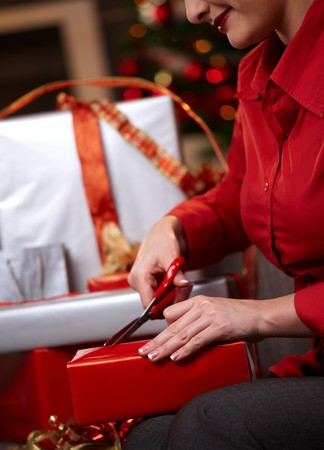 Closeup of wrapping christmas gifts, cutting wrapping paper with scissors. Stock Photo - 7791858