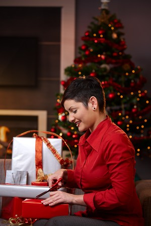 Happy young woman sitting on couch at home, wrapping christmas gifts, using scissors, smiling.   photo