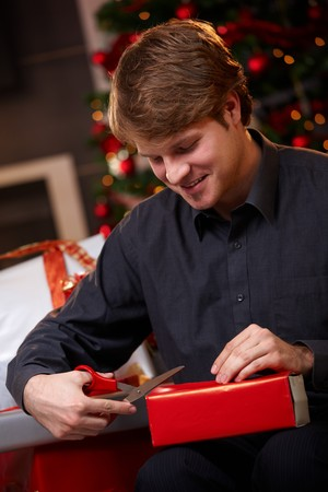 Happy young man sitting on couch at home, wrapping christmas gifts, using scissors, smiling.   photo