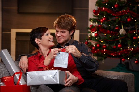Happy young couple giving presents at christmas, looking at each other, smiling.   photo