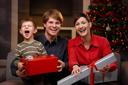 Happy parents and son sitting at couch, holding christmas gifts, laughing. photo