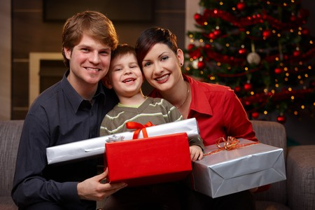 Portrait happy family at christmas, holding presents, smiling. photo