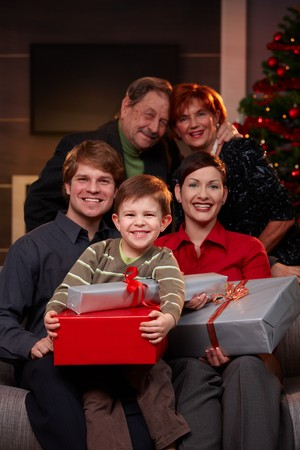 Portrait of happy family together with grandparents at christmas eve, holding presents, smiling.