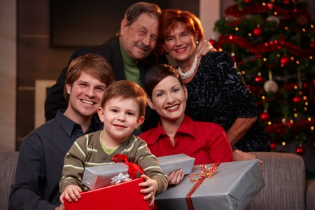 Portrait of small boy holding christmas gifts, together with parents and grandparents. photo