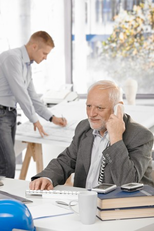 Senior businessman talking on landline phone sitting at office desk, young colleague working in background. photo