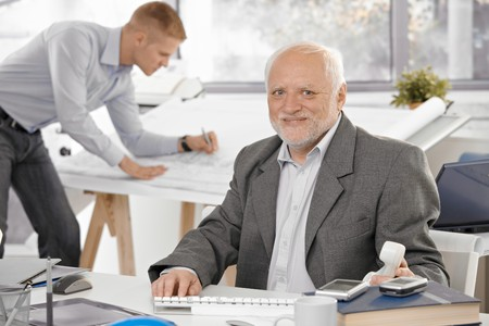 Senior businessman sitting at desk, smiling at camera, young architect working in office background. photo