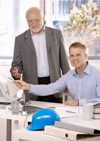 Portrait of senior and junior businessmen working together in office, smiling at camera, pointing at computer screen. photo