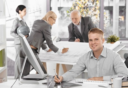 Architects busy at work, young designer in focus sitting at desk using drawing pad, smiling at camera. Stock Photo - 7791851