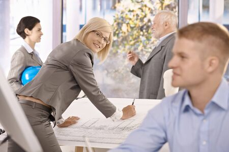 Architects working in office, female designer smiling at camera working on plan. Stock Photo - 7791857