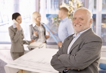 Proud smiling senior businessman standing with arms crossed, smiling, with team working in background. Stock Photo - 7791878
