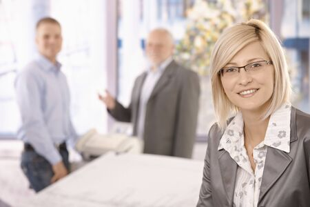 Portrait of smart businesswoman wearing glasses, smiling in office with coworkers in background. photo