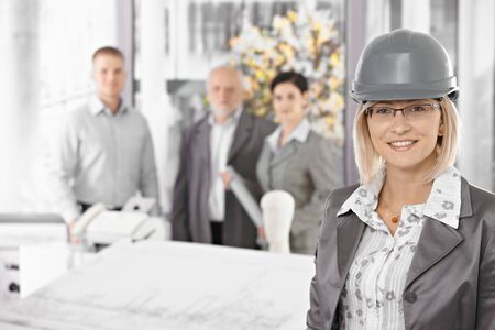 Businesswoman wearing hardhat in architectural office, team standing in background. photo