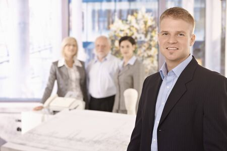 Young smiling businessman standing in office with team in background. Stock Photo - 7791847