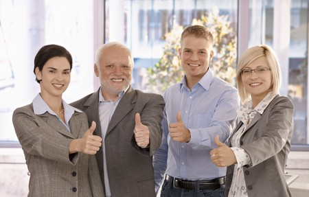 Successful businessteam giving thumbs up standing in bright office, smiling. photo