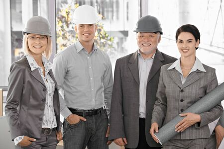 Confident team of architects wearing hardhat, holding plan, smiling at camera. photo