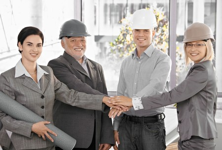 Architect team in office holding hands in unity, expressing teamwork, wearing hardhat, smiling at camera. photo