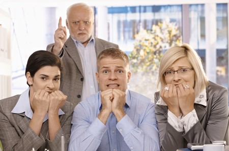Scared employees sitting with hands up to mouth, angry boss standing behind pointing. photo
