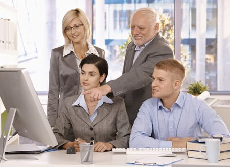 Experienced senior executive working with businessteam, pointing at computer screen, smiling. photo