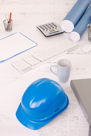Desk in architect office, with design plan, hardhat, coffee mug, calculator and notes. Stock Photo - 7791827