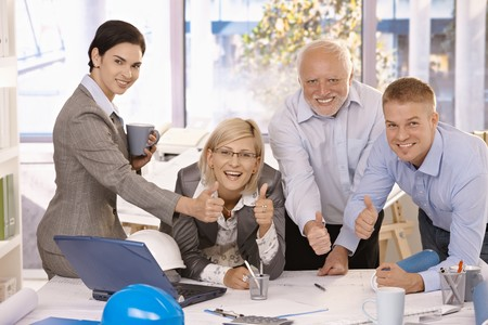 co worker: Portrait of happy businessteam giving thumbs up at work, smiling at camera. Stock Photo