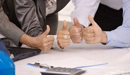 Closeup picture of 4 hands giving thumbs up in business office photo