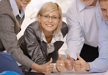 Smiling confident businesswoman giving thumbs up with team in office. photo