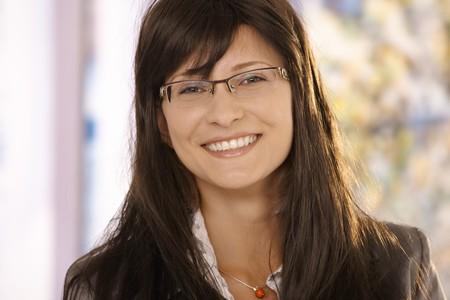 woman wearing glasses: Closeup portrait of mid-adult woman wearing glasses, smiling at camera.