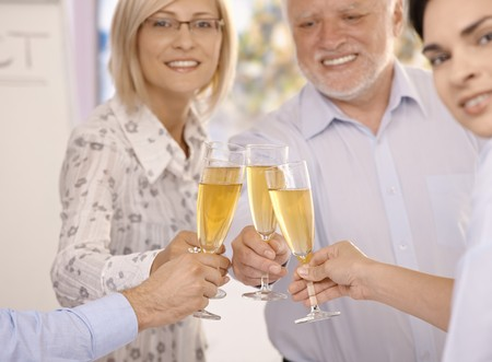 Businesspeople celebrating success with champagne, smiling, focus on glasses and hands. photo