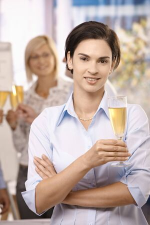 Portrait of businesswoman celebrating work success with champagne, colleagues in background. photo