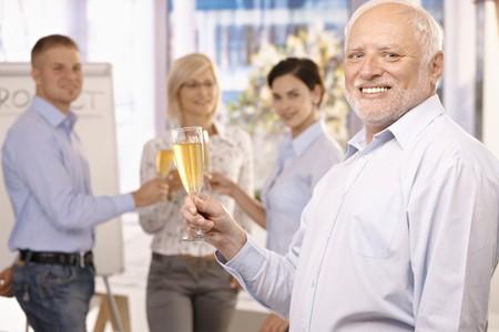 personas celebrando: Senior empresario elevar el vaso de champ�n para tostar, sonriendo a la c�mara, equipo celebrando en segundo plano.  Foto de archivo