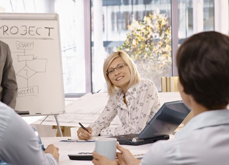 Smiling mid adult businesswoman sitting on team meeting, looking at camera. photo