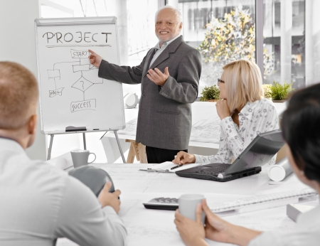 experienced: Senior businessman talking to colleagues, explaining project success, pointing at whiteboard, smiling. Stock Photo