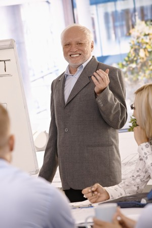 Portrait of senior businessman doing presentation in office, gesturing, smiling at camera. photo