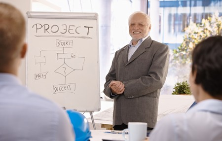Experienced senior businessman training group about project success in office, smiling. photo