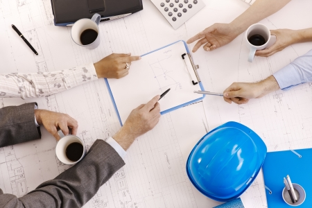 Businessmeeting, closeup hands of architects pointing at clipboard on office table. Stock Photo - 7791936
