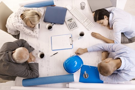 Tired businesspeople at meeting, sleeping leaning on table, high angle view. photo