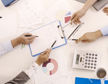 co work: Hands holding pen pointing at document at business meeting in closeup overhead view. Stock Photo