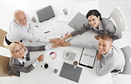 co worker: Confident businessteam holding hands at meeting over table expressing teamwork and unity, smiling at camera, overhead view.