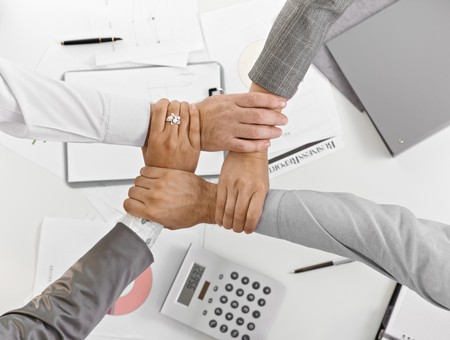 cooperating: Four hands in unity at businessmeeting in closeup, from high angle view, over table, expressing teamwork.