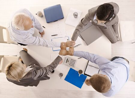 Businesspeople holding hands united over meeting table, while teamworking, high angle view. photo