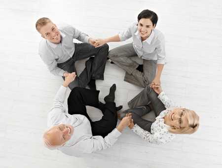 Smiling businessteam doing relaxation, looking at camera sitting on floor in lotus posture, high angle view. photo