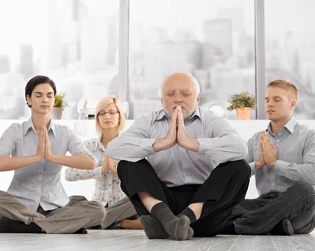 doing business: Businesspeople doing meditation in office with closed eyes, hands put together, concentrating. Stock Photo