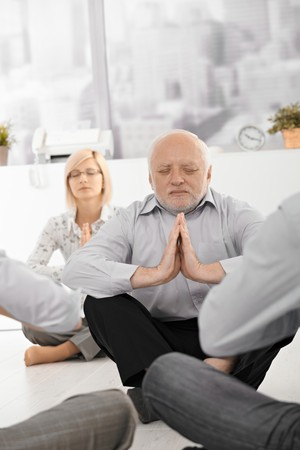 Senior businessman meditating in office with colleagues, eyes closed. photo
