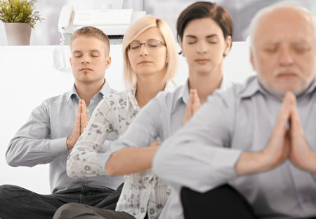 Businessteam doing yoga exercise in office together, sitting on floor with eyes closed. photo