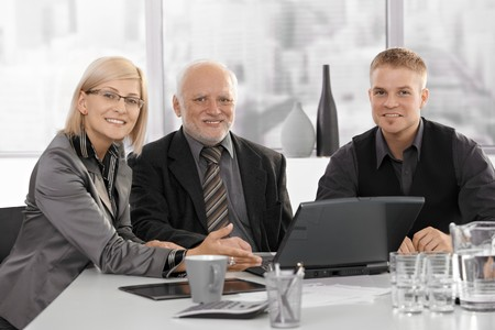 Businesspeople meeting with senior executive, sitting at table, smiling at camera. Stock Photo - 7791839