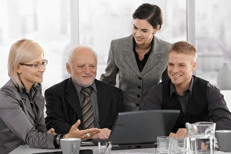businessteam: Smiling businessteam on meeting, mid-adult businesswoman showing computer work to coworkers. Stock Photo