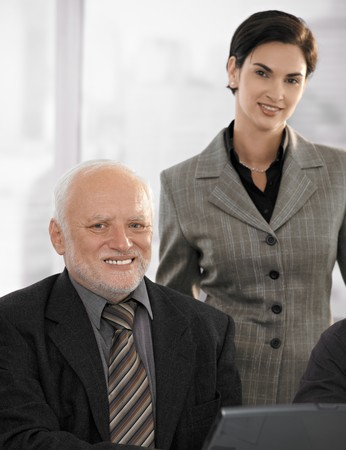 mid adult female: Portrait of senior businessman with mid adult female partner in office, smiling at camera. Stock Photo